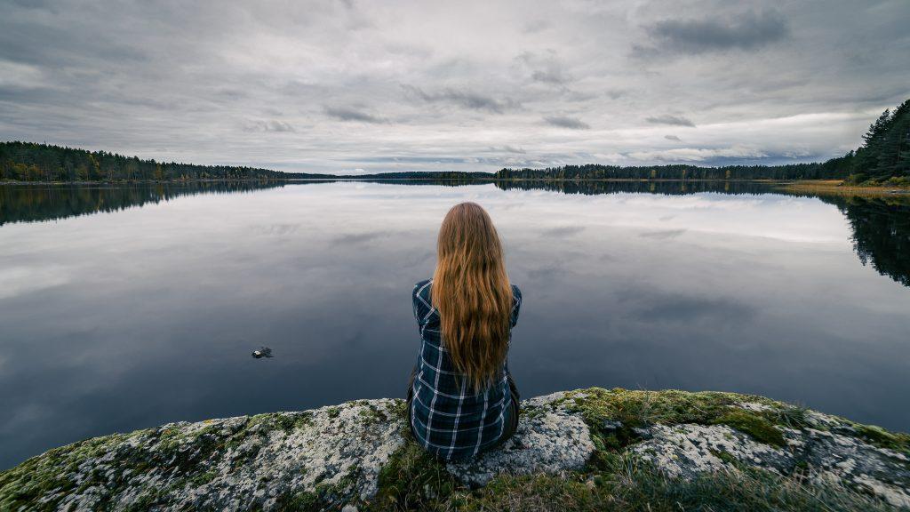 Kaunis peilityyni järven pinta ja istuja kivellä.
