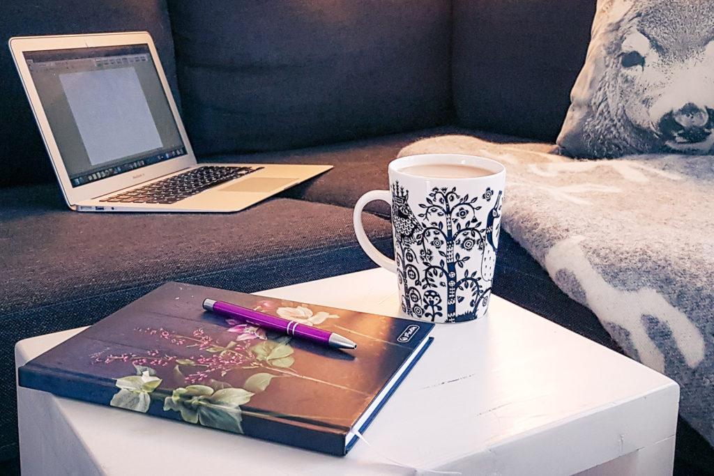 Kahvikuppi ja tietokone sommitelma.