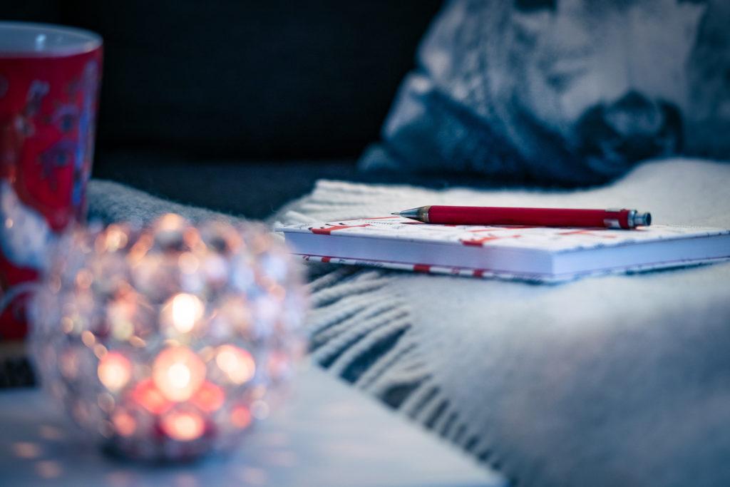 Kirjoitusvihko ja kynttiläkippo sommitelma.