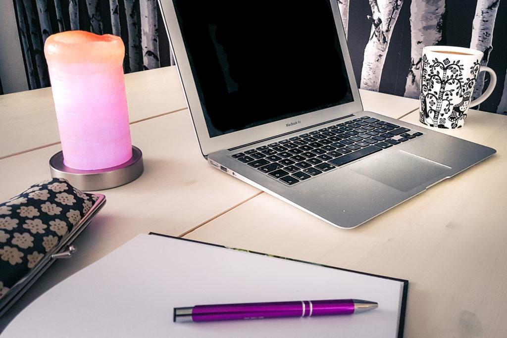 Tietokone ja kirjoitusvihko pöydällä.