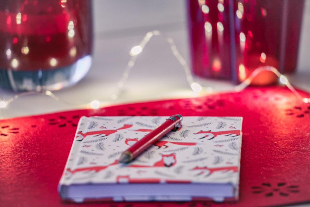 Kirjoitusvihko ja kynä pöydällä.