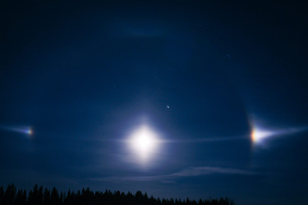 Haloilmiö sivuauringot kuun ympärillä.