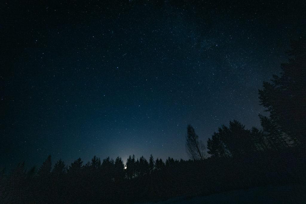 Öisellä taivaalla näkyvä tähdenlento.