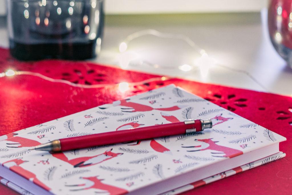 Vihko ja kynä pöydällä.