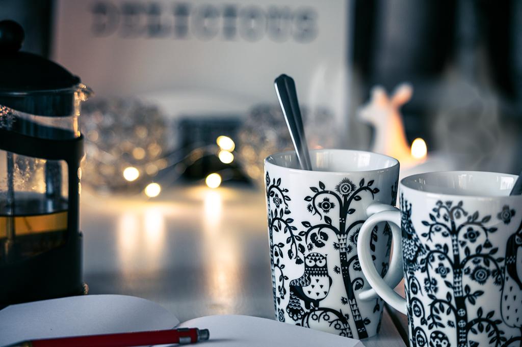 Teekupit ja kirjoitusvihko pöydällä.