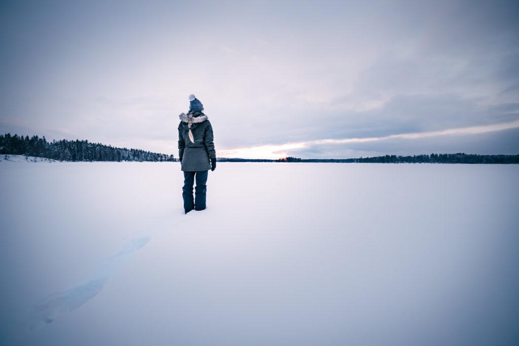Henkilö seisomassa järvellä.