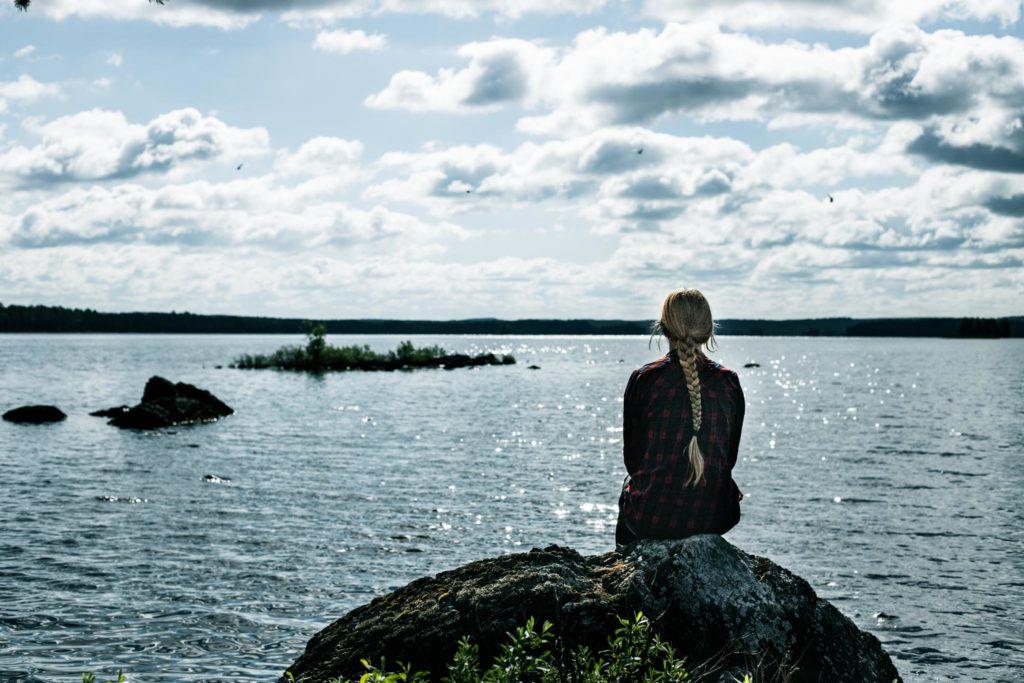 Istumassa kivellä järvimaisemassa.