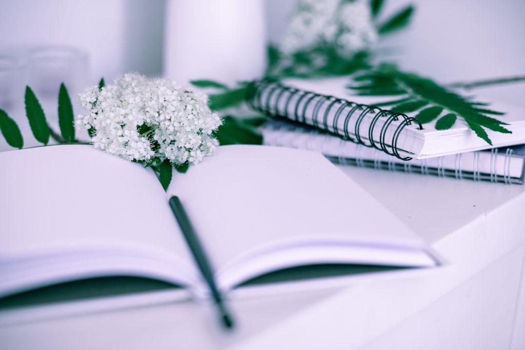Kirjoitusvihko ja kynä.