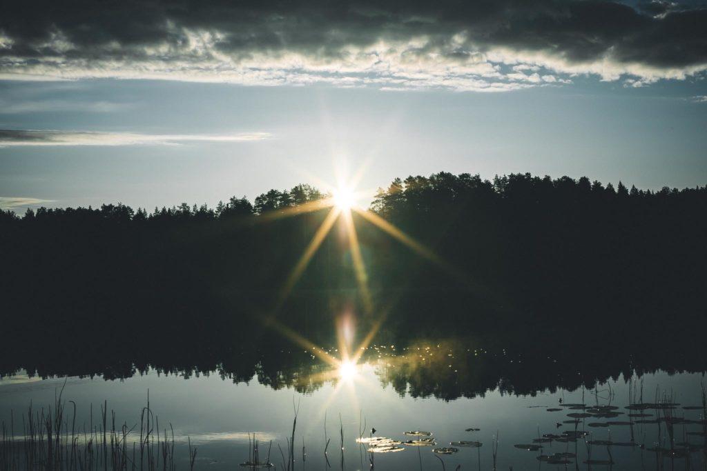 Aamuaurinko nousee järven takaa.