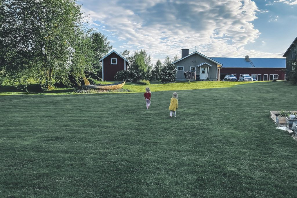 Lapset juoksemassa nurmikolla.