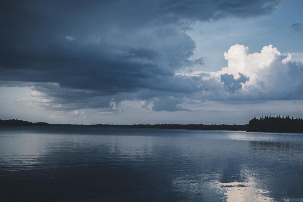 Uhkaavan näköiset sadepilvet järvellä.